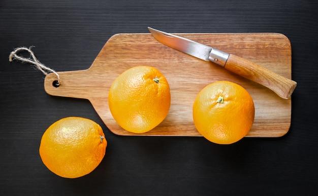 Laranjas e canivete tradicional em uma tábua de madeira
