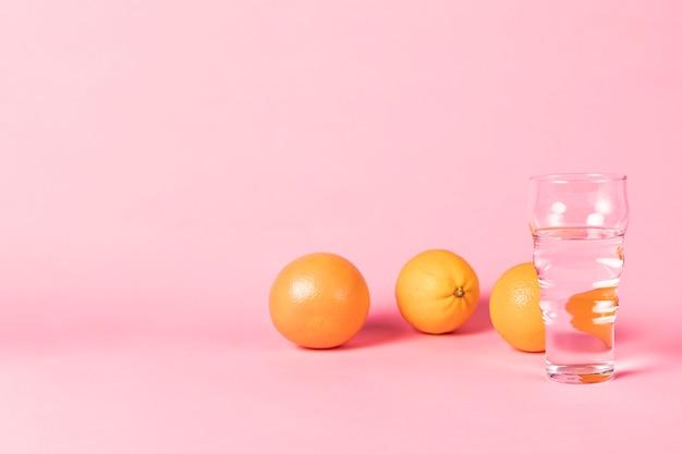 Laranjas e copo de água com espaço de cópia
