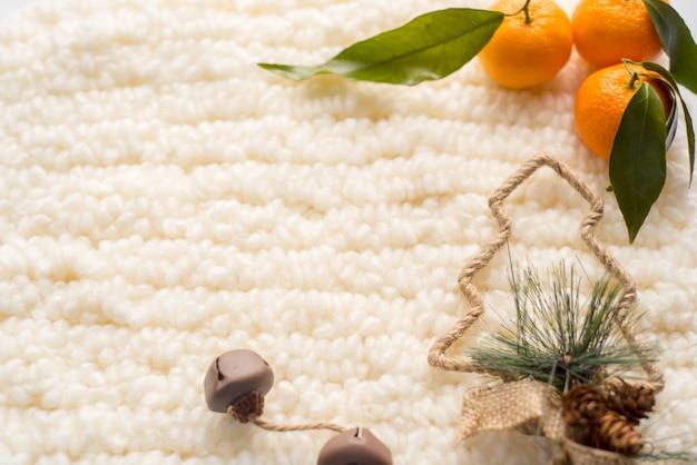 Laranjas e enfeites de árvore de natal no lenço branco