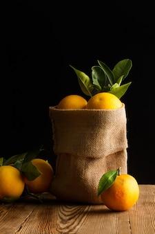 Laranjas em um saco de estopa e sobre uma mesa de madeira com fundo escuro