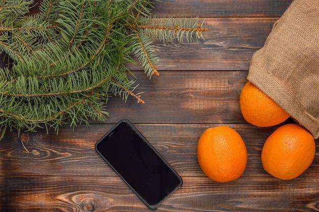Laranjas em um saco de linho em uma superfície de madeira perto de ramos de pinheiro e smartphone preto natal