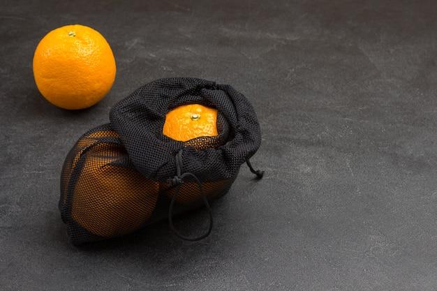 Laranjas em um saco de malha reutilizável. conceito ecológico. copie o espaço. superfície preta. vista do topo