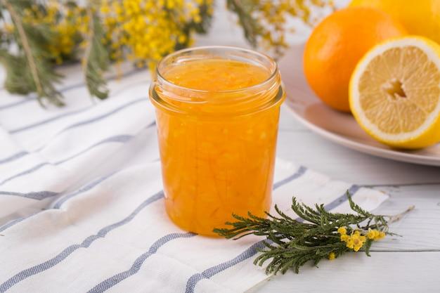 Laranjas fatiadas e geléia de laranja em uma jarra de vidro