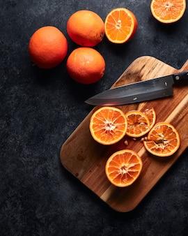 Laranjas fatiadas e uma faca sobre uma tábua sobre uma mesa preta