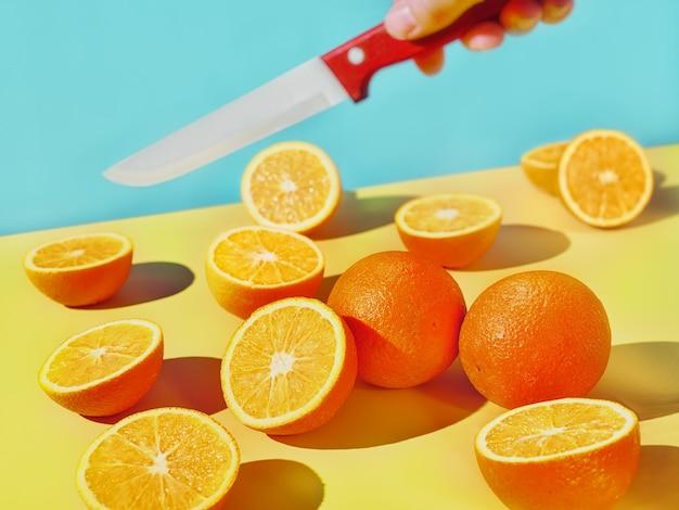 Laranjas fatiadas e uma faca vermelha