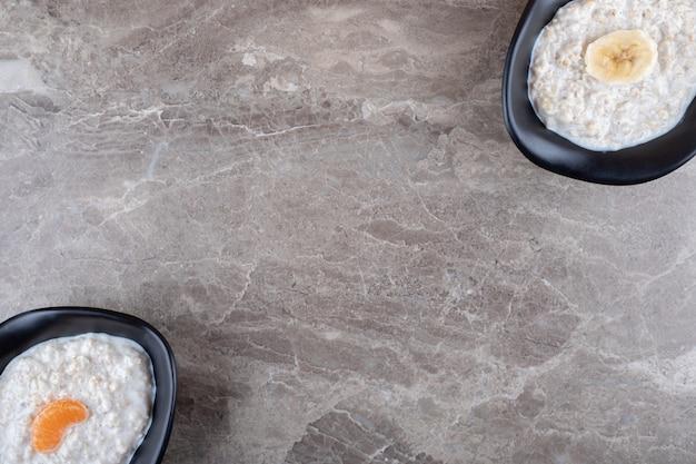 Laranjas fatiadas em uma tigela de mingau ao lado de banana fatiada em uma tigela de mingau, na superfície de mármore