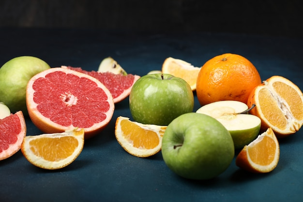 Laranjas fatiadas, toranja e maçãs verdes sobre o fundo azul.