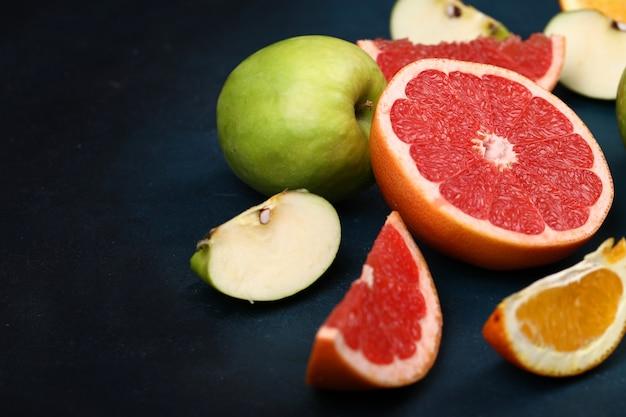 Laranjas fatiadas, toranjas e maçãs verdes.