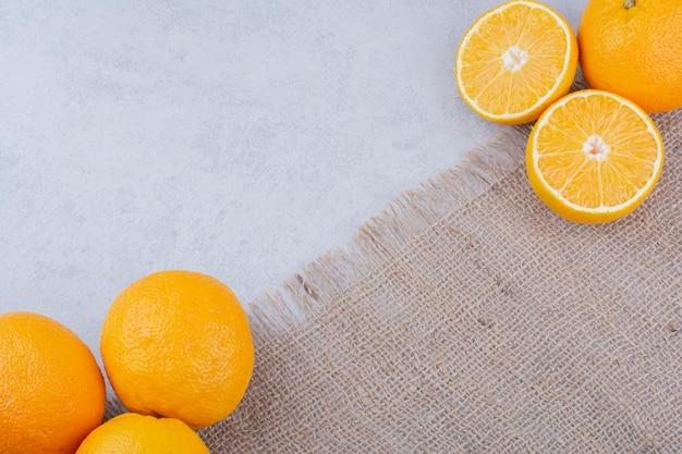 Laranjas frescas deitado de saco no fundo branco. foto de alta qualidade