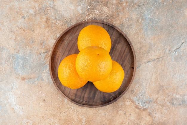 Laranjas frescas e azedas em um prato de madeira