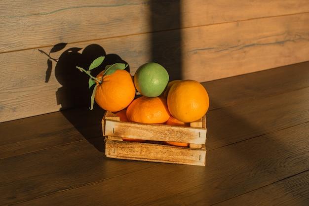 Laranjas frescas em iluminação natural de caixa de madeira sobre uma superfície de madeira