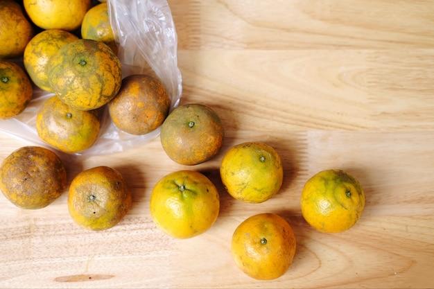 Laranjas frescas frutas um saco de plástico transparen na mesa de madeira
