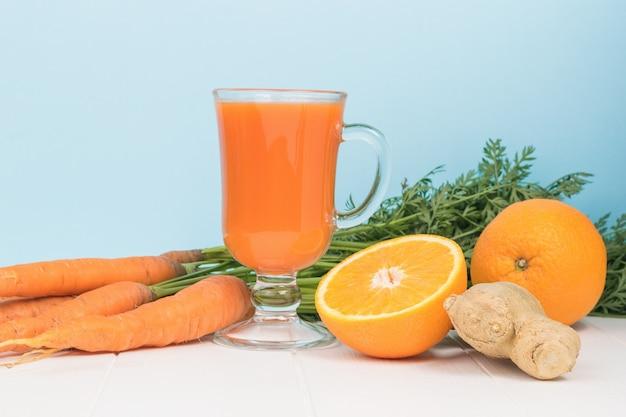 Laranjas, gengibre, cenoura e um copo de smoothies em uma mesa de madeira.