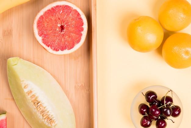 Laranjas inteiras; cerejas vermelhas; toranja e muskmelon cortados ao meio na mesa de madeira