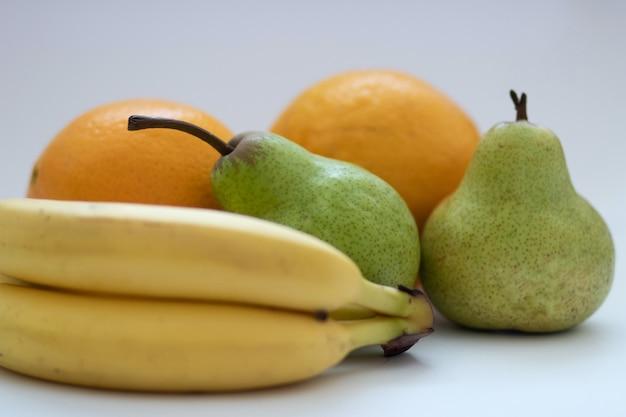 Laranjas, peras e bananas em um fundo branco e isolado