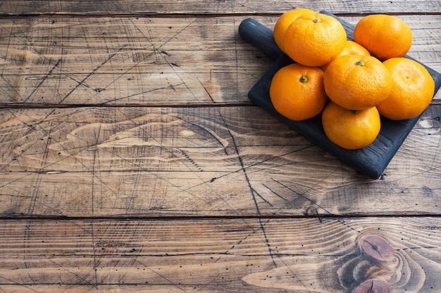Laranjas, tangerinas ou tangerinas clementinas, frutas cítricas em fundo de madeira rústico, copie o espaço.