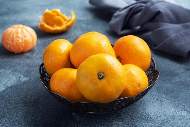 Laranjas, tangerinas ou tangerinas clementinas, frutas cítricas em uma mesa escura.