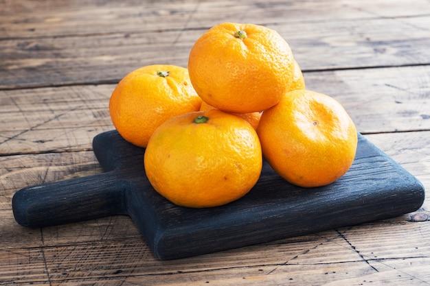 Laranjas, tangerinas ou tangerinas clementinas, frutas cítricas na mesa de madeira rústica, copie o espaço.