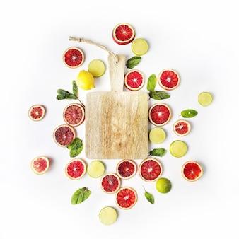 Laranjas vermelhas, limões amarelos, limas verdes, hortelã e tábua de cortar isoladas em branco