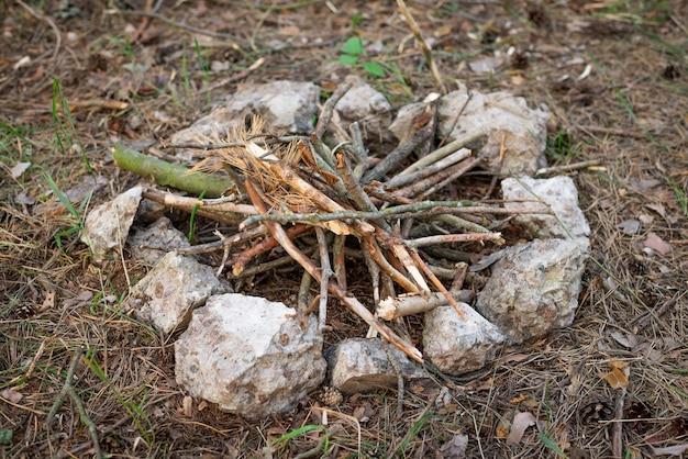 Lareira a lenha na floresta com pedras ao redor para evitar incêndios florestais