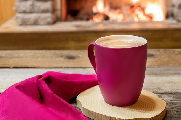 Lareira aconchegante e uma xícara de chá com leite, em casa de campo, férias de inverno.