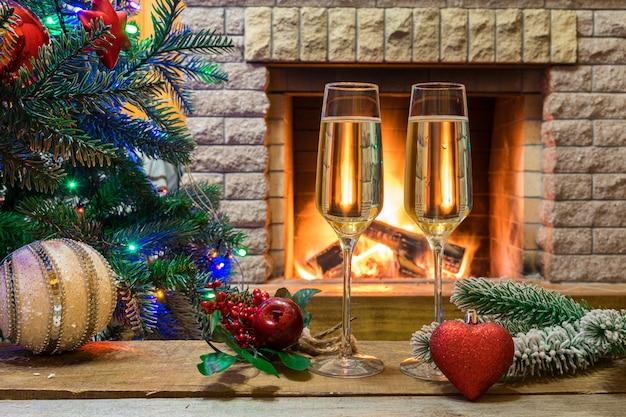 Lareira aconchegante. vinho champanhe antes da árvore de natal decorada brinquedos e luzes de natal na casa de campo.