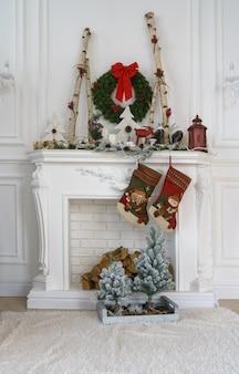Lareira branca decorada para o natal com pequenas árvores de natal e meias vermelhas