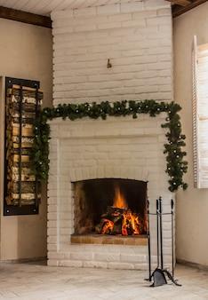 Lareira de tijolo branco decorada com uma guirlanda de natal