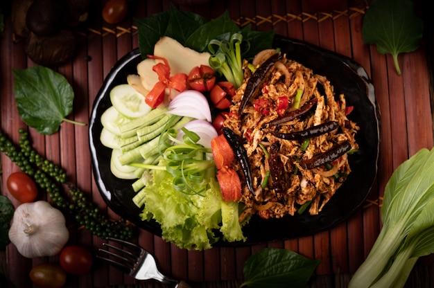Larva de frango no prato com pimenta-malagueta seca, tomate, cebolinha e alface