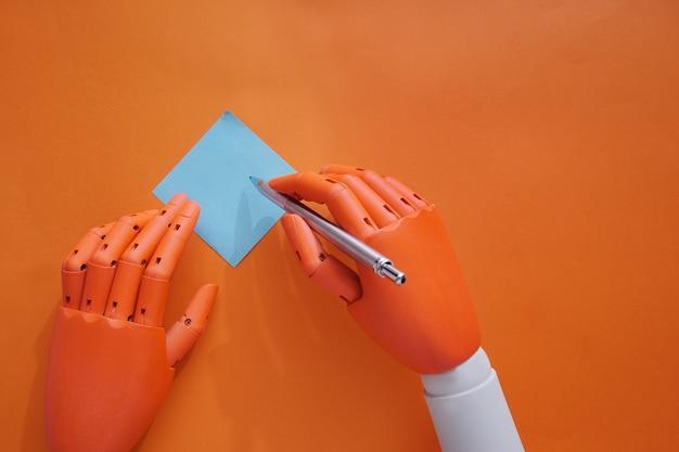 Las manos del maniqu hacen una nota sobre un fondo naranja
