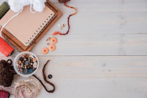 Lãs; miçangas; corda; carretel na mesa de madeira