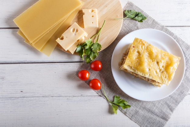 Lasanha com carne e queijo triturados na superfície de madeira branca.