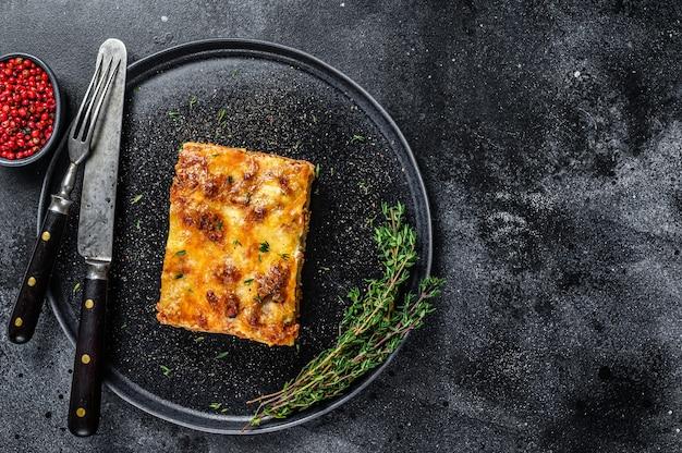 Lasanha com carne picada de carne bovina e molho de tomate à bolonhesa em um prato. fundo preto. vista do topo. copie o espaço.