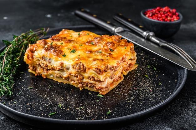 Lasanha com carne picada de carne bovina e molho de tomate à bolonhesa em um prato. fundo preto. vista do topo.