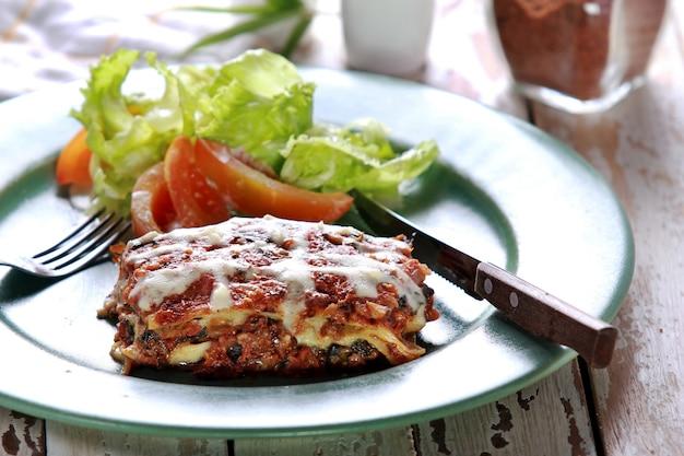 Lasanha de carne italiana servida com salada em prato verde com garfo e faca