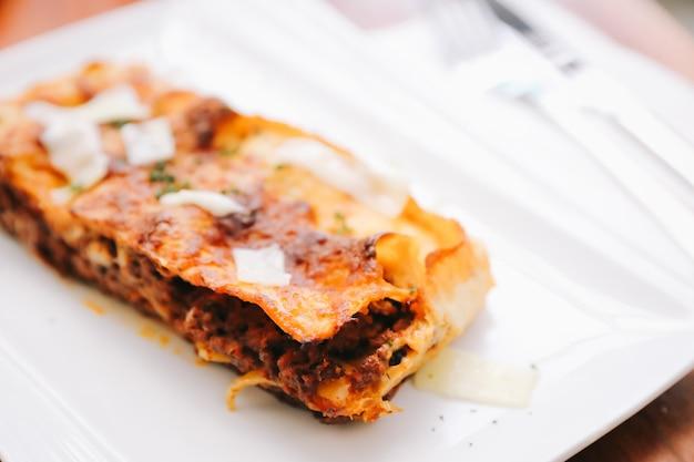 Lasanha de carne no fundo de madeira, comida italiana