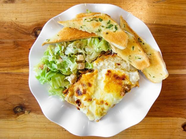 Lasanha deliciosa com salada de legumes e pão