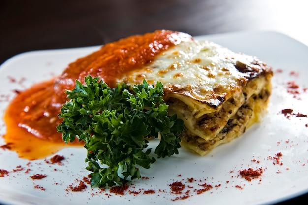 Lasanha dourada com carne, tomate, molho de queijo e macarrão em camadas alternadas sobre uma tábua de madeira guarnecida com manjericão
