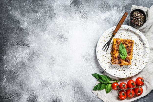 Lasanha italiana caseira com molho e carne de tomate. fundo cinza. vista do topo. espaço para texto