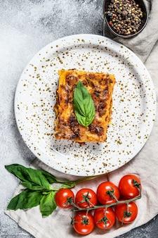 Lasanha italiana caseira com molho e carne de tomate. fundo cinza. vista do topo