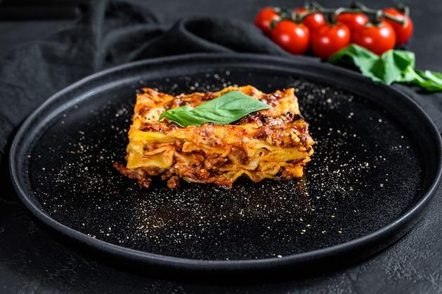 Lasanha italiana caseira com molho e carne de tomate. fundo preto. vista do topo