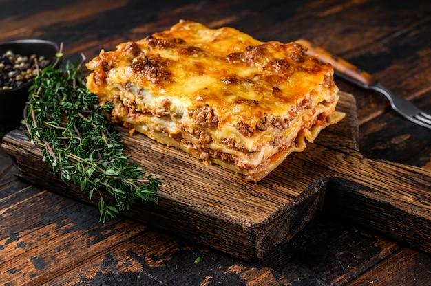 Lasanha italiana com molho à bolonhesa e carne moída de boi. fundo de madeira escuro. vista do topo.