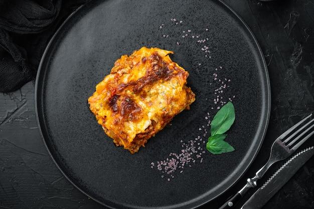 Lasanha italiana com molho de tomate à bolonhesa e carne picada de carne bovina, no prato, na mesa de pedra preta, vista de cima, plano plano