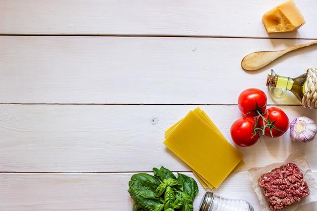 Lasanha, tomate, carne picada e outros ingredientes. fundo de madeira branco. cozinha italiana.
