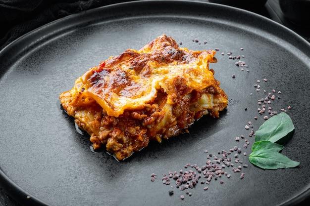 Lasanha tradicional feita com molho de carne picada à bolonhesa coberta com folhas de manjericão,