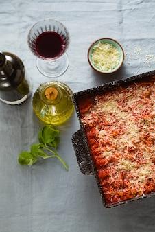 Lasanha vegana com lentilhas e ervilhas verdes em uma assadeira sobre uma mesa com uma toalha de mesa de linho azul. e vinho tinto em copos