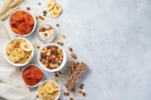 Lascas de banana, damascos secos, diferentes tipos de nozes, passas e barra de granola dentro de tigelas brancas