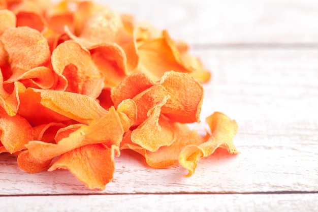 Lascas de cenoura desidratadas secas. delicioso lanche ecológico e orgânico para toda a família. conceito de alimentação saudável.