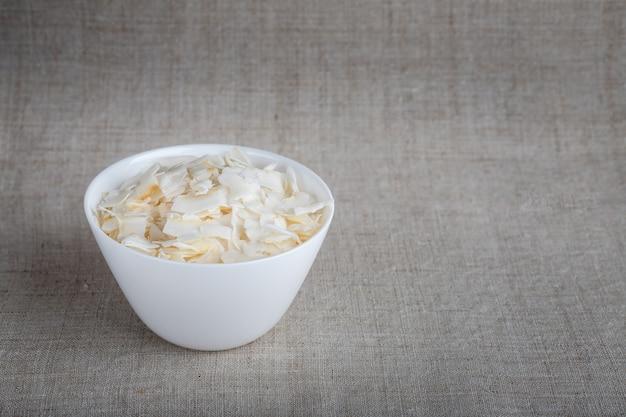 Lascas de coco em uma tigela sobre a mesa