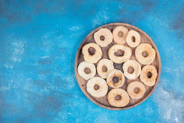 Lascas de maçã secas na placa de madeira na superfície azul
